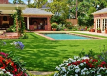 Modern-shaped-swimmng-pool-with-landscaping-arbor-patio-cove-and-outdoor-ktichen