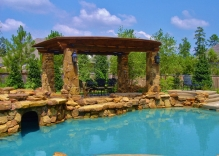 Tropical-pool-with-cave-arbor-with-stone-column-bases