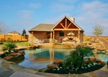 beach-entry-swimming-pool-with-water-slide-and-large-cabana-with-outdoor-kitchen