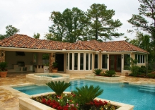 mediterranean-style-pool-and-spa-surrounded-by-small-flower-beds-and-patio-cover-with-outdoor-kitchen