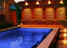 Night-Shot-modern-swimming-pool-spill-over-edge-arbor-and-louvered-wall.-concrete-stepping-stones-and-mexican-beach-pebbles